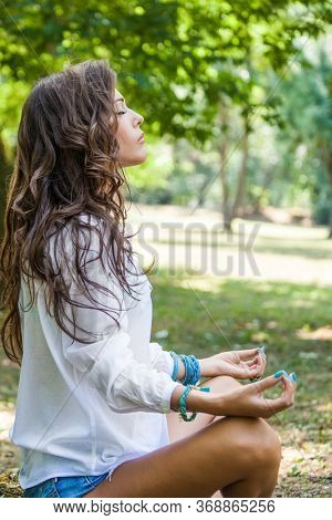 young woman meditate and practice breathing in park body and mind benefit summer day side view yoga meditation