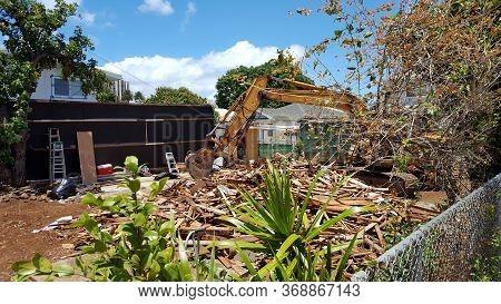Honolulu - April 21, 2016: Construction Bulldozer Tears Down Home Of Lot In Kapahulu On Oahu, Hawaii