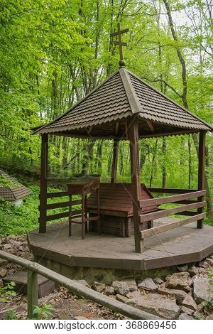 Wooden Arbor With A Well In The Forest On A Background Of Green Trees