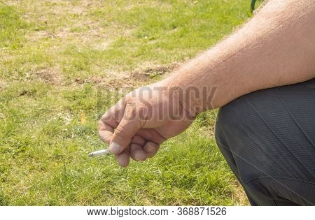 Close-up Of An Elderly Man's Hand Holding A Cigarette And Smoking Against An Open Nature Bokeh. Conc