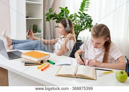 Mother Is Not Helping Daughter To Do Homework While Using Her Smart Phone And Listening To Music Wit