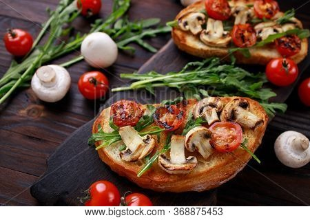 Tasty Homemade Italian Antipasti Bruschetta With Chopped Tomatoes, Champignons And Arugula, Healthy