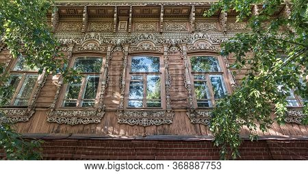 Windows Of An Old Residential Building With Wooden Carved Platbands