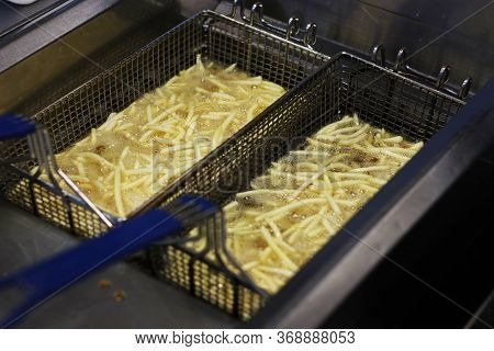 Cooking French Fries. Close Up Of Frying French Fries In The Fryer In Hot Oil