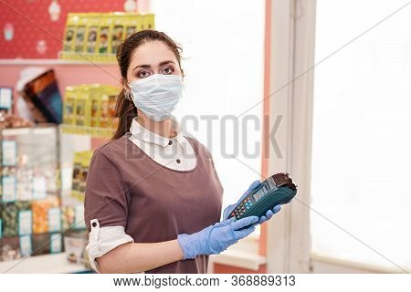 Small Businesses During The Pandemic. Portrait Of A Female Worker In A Medical Mask And Rubber Glove