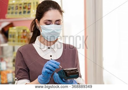 Small Businesses During The Pandemic. Portrait Of A Worker In A Medical Mask Holding A Bank Terminal