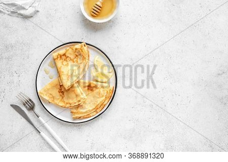 Crepes With Lemon And Honey On White Background, Top View, Copy Space. Homemade Recipe Of Thin Crepe