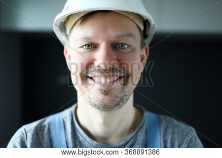 Happy Builder Man In Helmet Stands In Apartment. Man Is Standing In Room And Smiling. Work Is Perfor