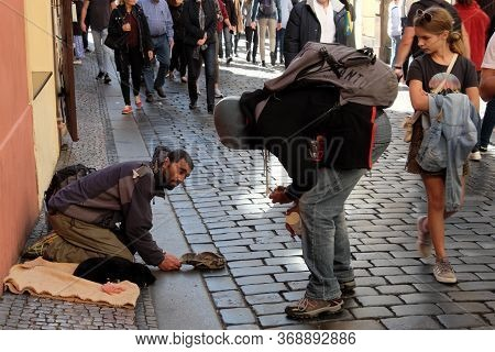 Prague, Czech Republic, October 12, 2019. A Girl Watches A Guy Chatting With A Beggar. Migrant Begs