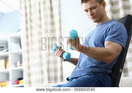 Guy Sitting Home Simulator And Looking At Dumbbells. Work Out Different Muscle Groups Evenly. Muscle