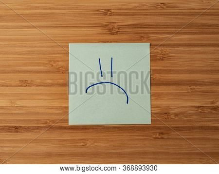 A Paper Sticker Pasted On A Wooden Surface With The Image Of The Symbol Of A Sad Emoticon