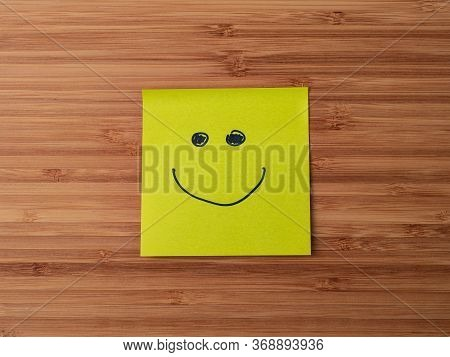 A Paper Sticker Pasted On A Wooden Surface With The Image Of The Happy Smiley Character