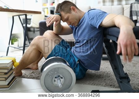 Tired From Sports Exercises Guy Sits Floor At Home. Useful Space In Apartment For Sports. Fatigue Fr