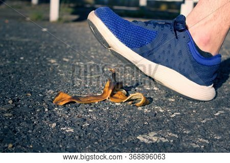 Caution, Risk Of Slipping.the Man Will Slip Over The Banana Peel In A Moment.the Men`s Shoe Almost T