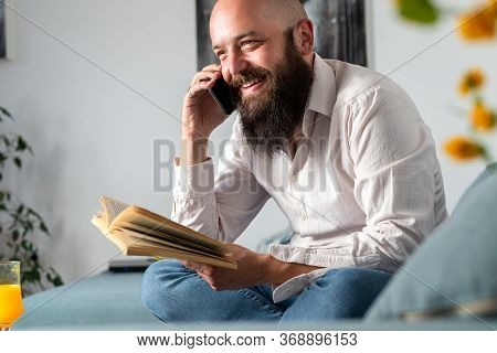 Man Speaking On Cell Phone. Bearded Man Speaking On Cell Phone And Reading Book. Happy Young Man Spe