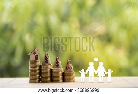 Loving Family, Us Money Bags On Rows Of Rising Coins On Table. Concept Planning For A Secure Future