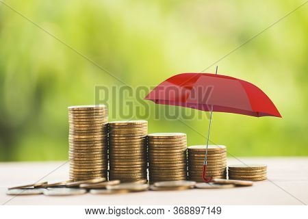 Red Umbrella Protects Rows Of Increasing Coins On Table. Concept Long Term Money Investment And Weal