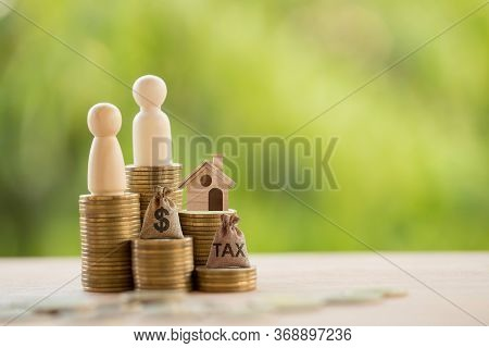 Couple And Home Model On Rows Of Rising Coins, Us Dollar Bags On A Table. Concept House Or Building
