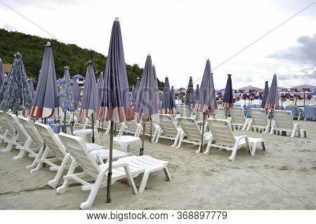 Beach Chairs Or Sun Loungers And Umbrellas On The Sandy Seashore At Koh Larn Island, Pattaya, Thaila