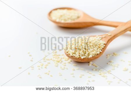 White Sesame Seeds In A Wooden Spoon On White Background. White Sesame Is Rich In Calcium And Phosph