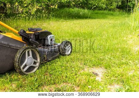 Lawn Mower On Green Grass In Garden Near The Forest. Machine For Cutting Lawns. Summer Work On The F