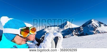 Two Adult Women Skiers Stand On The Background Of The Top Of The Mountain