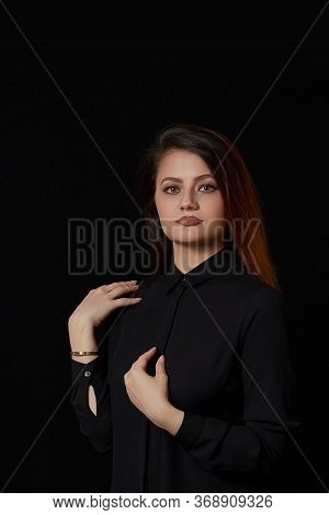 A Young Beautiful Muslim Woman With Brown Hair In A Black Blouse And Black Leather Skirt On A Black
