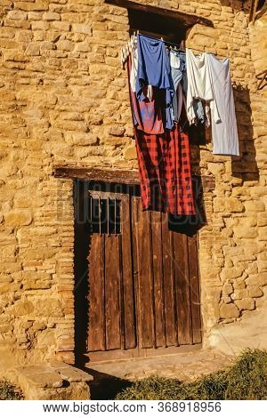 Facade Of Old House With Wooden Door And Clothesline Hanging Clothes At Puente La Reina. A Medieval