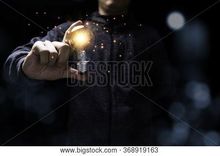 Businessman Holding Glowing Lightbulb With Orange Light . Creative New Business Idea Concept.