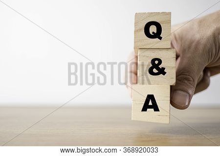 Hand Holding Wooden Cubes For Q&a Or Question And Answer. Training Meeting And Discussion Concept.