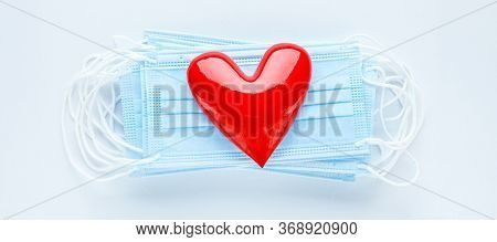 Bright red heart on a pile of medical face masks. Concept of support, love, care and a thank you to the frontline essential workers and healthcare workers.