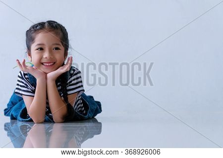 Cheerful Little Cuts Girl Smile Felling Relax While Lying Down On The Floor With Copy Space At Home.