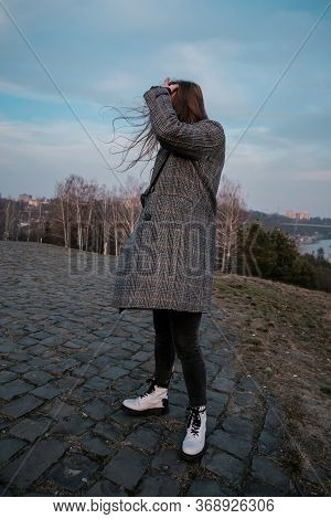 Young Woman Standing On Street With Hair Blown By The Wind, Covering Her Face. Young Casual Girl Wit