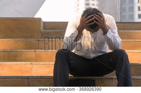 Business Men Bankruptcy And Debt Sitting On The Stairs With Hands Close His Head. Unemployed Busines