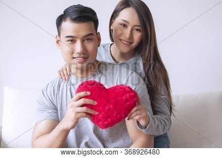 Sweetheart Young Couple Embracing Together While Holding Red Heart In Their Hands At Living Room. Ha