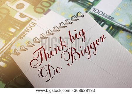 Text: Think Big Do Bigger Handwritten Lettering On The Page Of Spiral Copybook Put On 100 Euro Bills