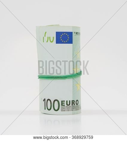 Banknotes One Hundred 100 Euros In A Roll With An Elastic Band. European To Save. Close-up, White Ba