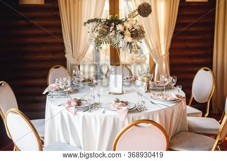Festive Table Setting With Empty Wine Glasses And Fresh Flowers