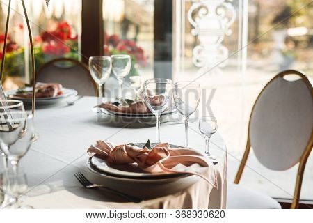 Close Up Festive Table Setting With Empty Wine Glasses And Pink Napkin