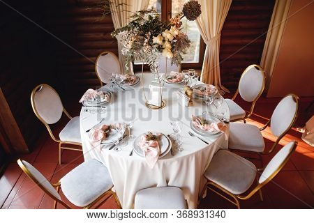 Festive Table Setting With Wine Glasses, Fresh Flowers And Tables With Number