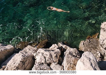 Sexy Woman In Bikini Lying On The Water. Attractive Young Woman Enjoying Summer Sun. Beautiful Lagoo