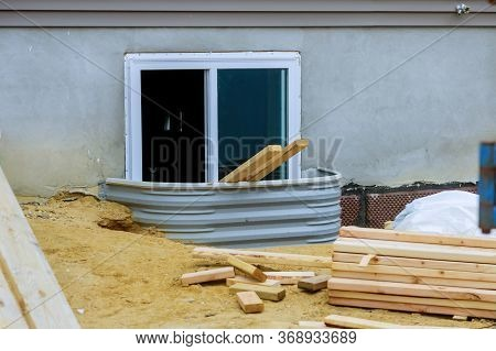 Stack Of Unloading Wooden Beams On Window Well On Basement Construction Building Site From Beam Cons