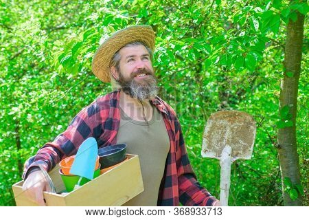 Smiling Man In Garden. Plants. Garden Tools. Gardening. Eco-farm. Work In Garden. Bearded Man With G