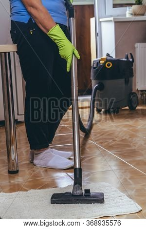 A Woman Vacuum Cleanses A Carpet In The Kitchen With A Vacuum Cleaner. Cleaning Of The Apartment. Go