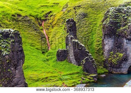 Cliffs covered with moss. The mysterious canyon in Iceland -  Fyadrarglyufur. Iceland. The summer day. River with glacial water flows between bizarre cliffs. The concept of active and photo tourism