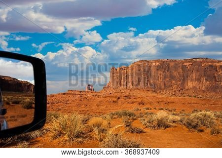 Monument Valley is a unique geological formation. The USA. Huge masses of red sandstone - outliers on the Navajo Indian Reservation. Reflection in a car mirror. The concept of photo tourism