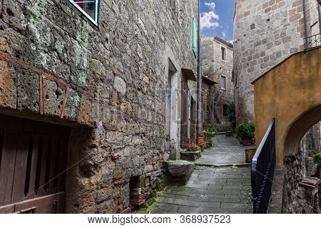 Italy, Tuscany. The tufa city of Sorano is enchanted city from a fairy tale. The narrow streets, stone steps and flower pots with blooming cyclamens. The concept of active, historical, photo tourism