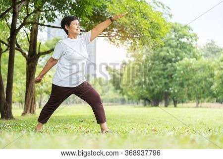 Relaxed Asian Senior Woman In White Cloth Doing Stretching Workout Her Arms At Park. Smiling Elderly