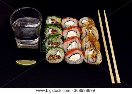 Sushi With Chopsticks, A Glass Of Sake And Lime On A Black Background