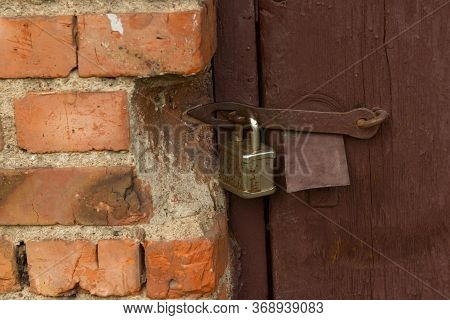 Rusty Locked Padlock On A Wooden Dilapidated Door Of A Pauper Dwelling Or Barn Shed